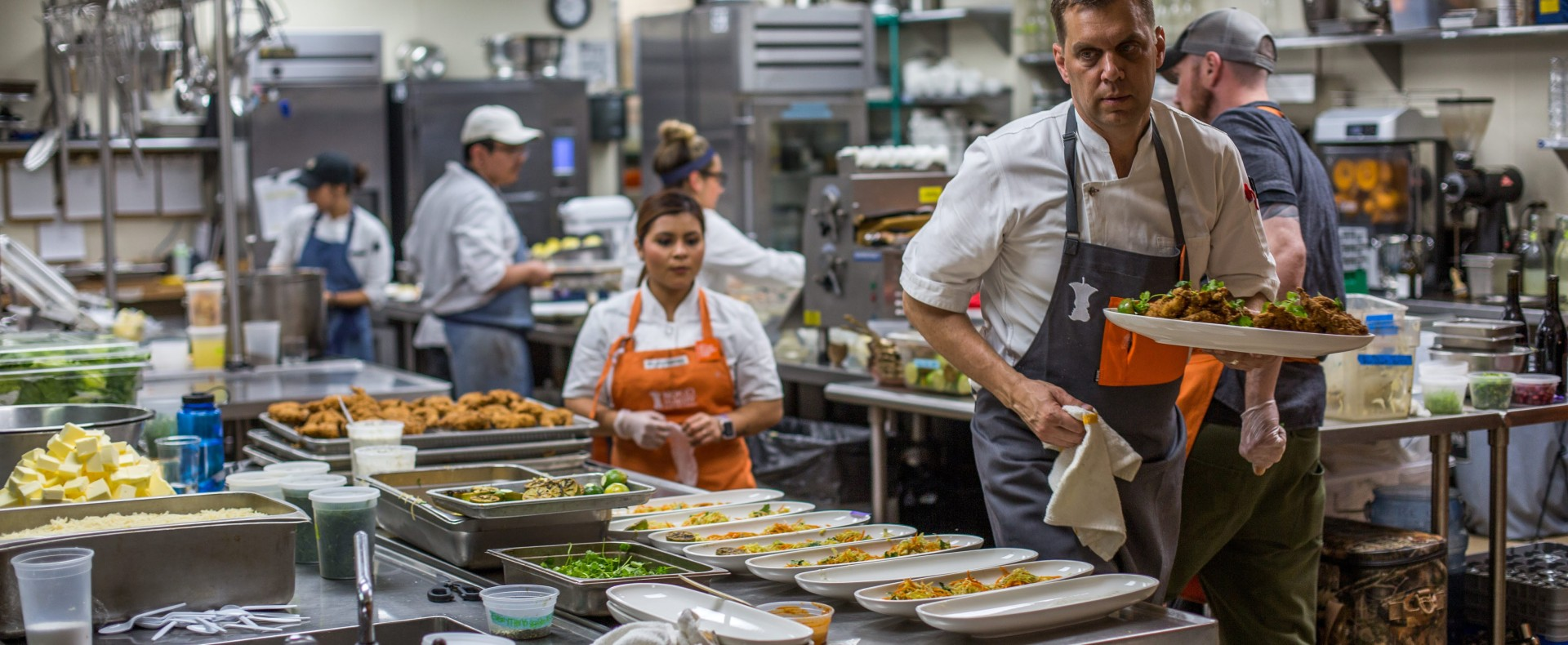 Chefs wearing No Kid Hungry aprons in a busy kitchen