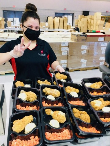 Woman wearing mask in front of trays of food