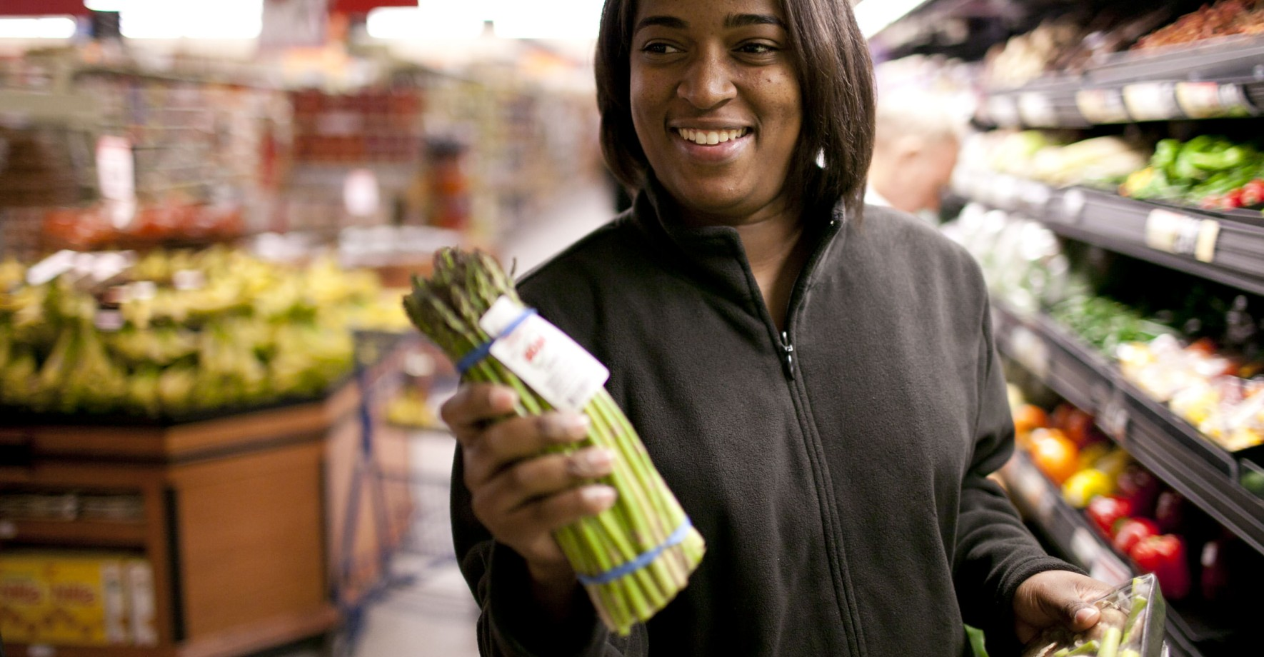 Woman holding asparagus bunch in grocery store