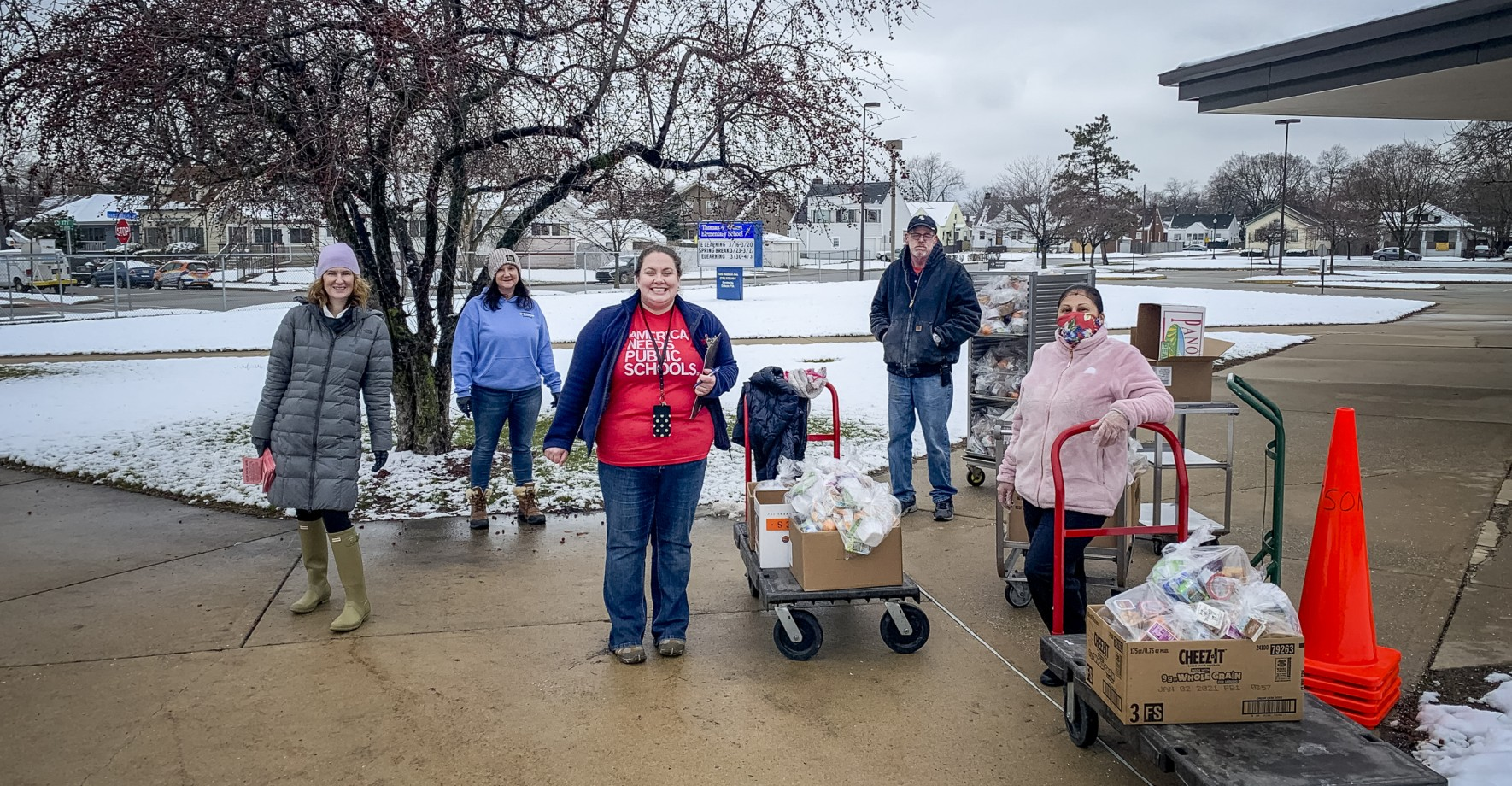 Food service staff pose outside in the snow, ready with carts of food to feed kids.