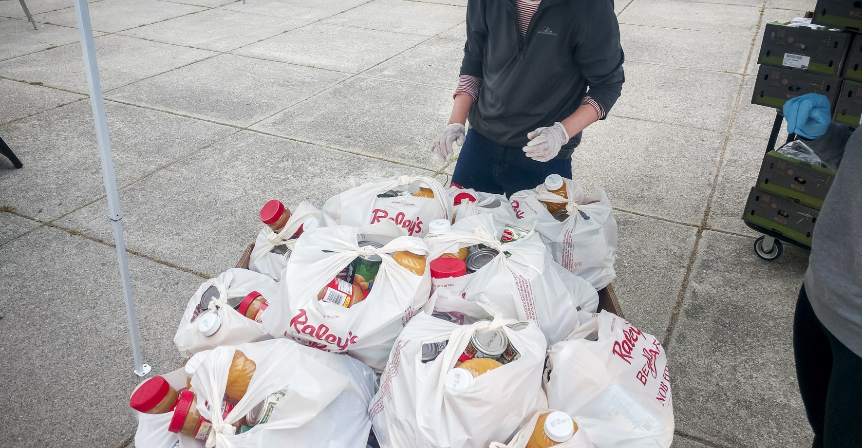 Volunteer prepares bags of food for distribution at a meal site during coronavirus closures.