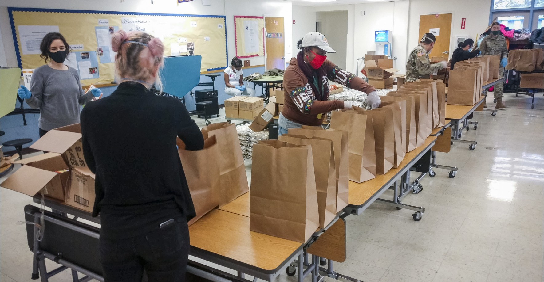Volunteers with the Oakland Unified School District prepare packages at a meals site.
