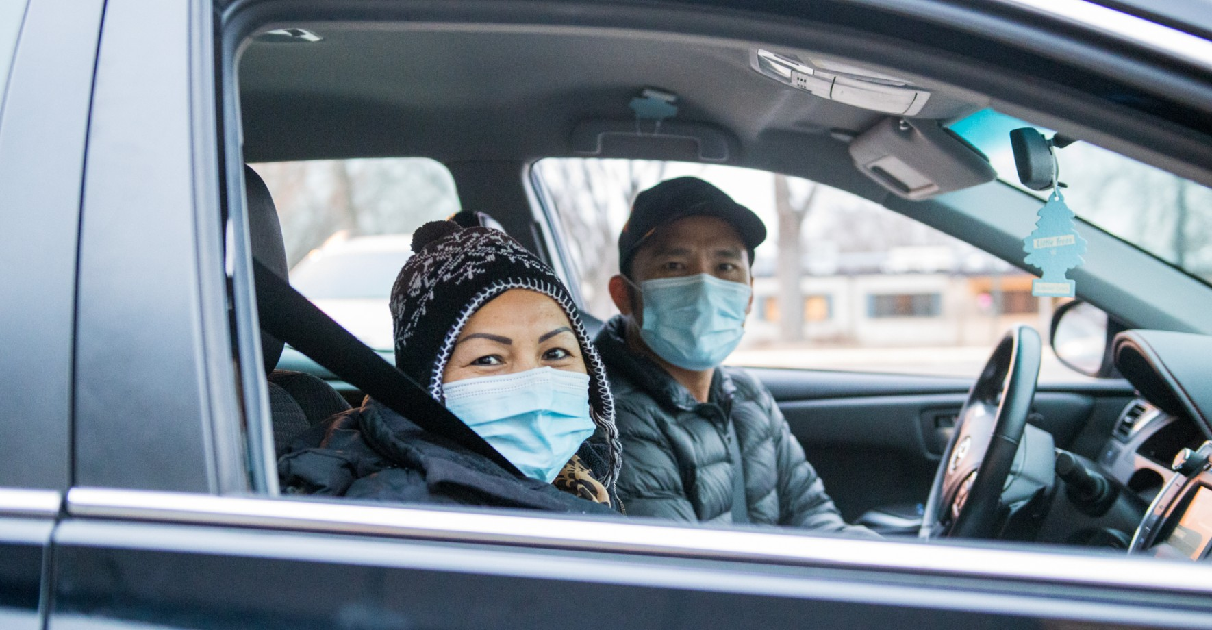 Two people in car wearing masks