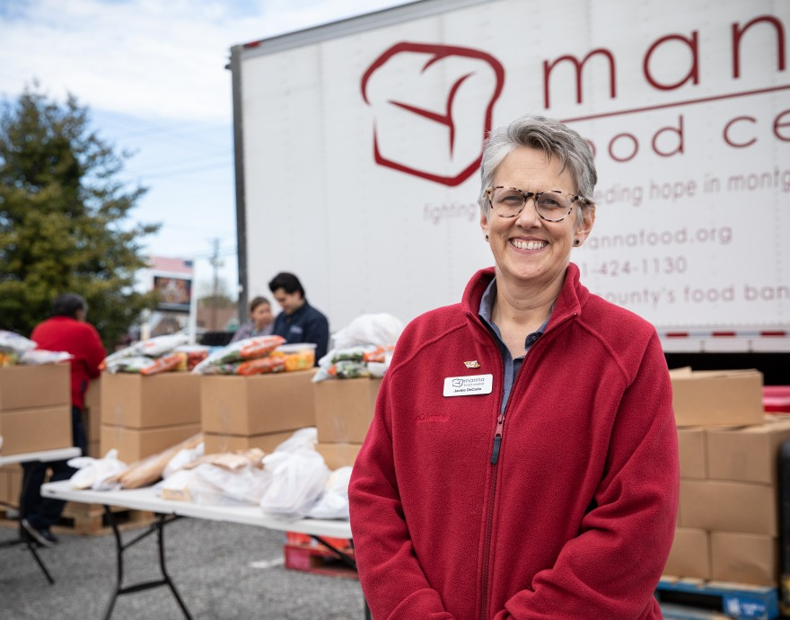 Manna Food Center's Jackie DeCarlo smiles in front of table full of food bags.