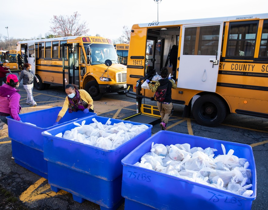Manna Food Center staff and volunteers load school buses with food bags.