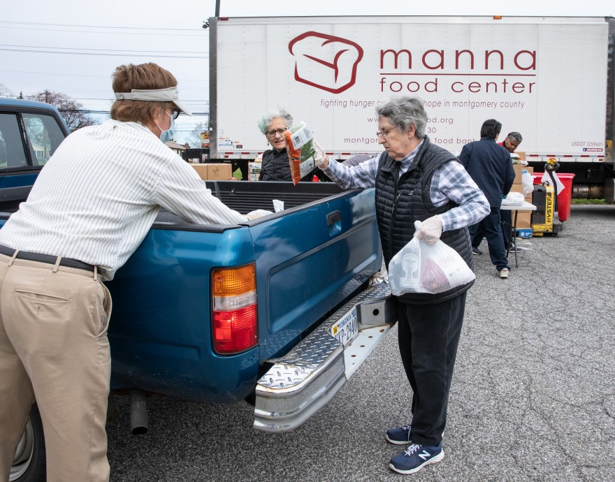 Volunteers place food bags in the bed of a truck.