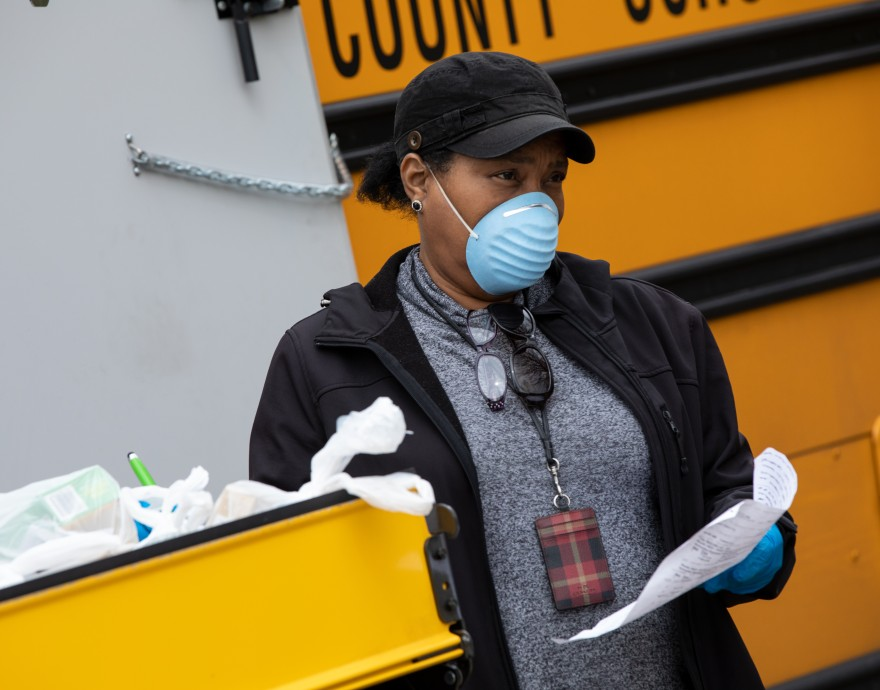 A woman in a mask stands by a school bus and cart of food bags.