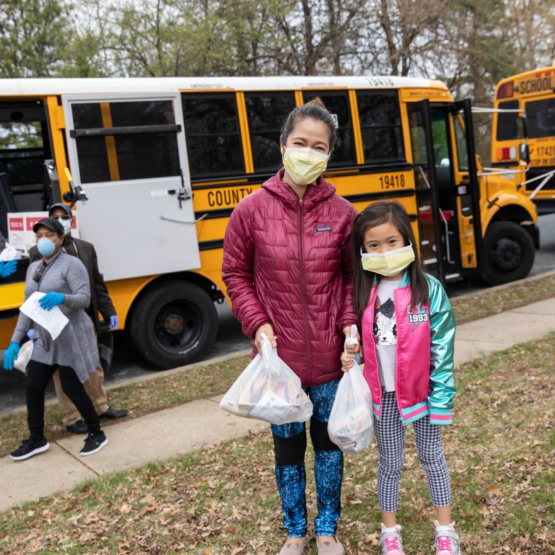 A mother and daughter wear face masks and carry their meals away from the school bus.
