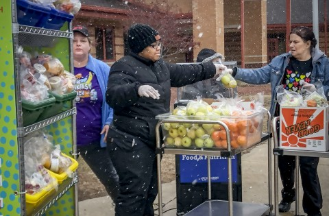 Three food service workers handle bags of fruit outside in the snow.